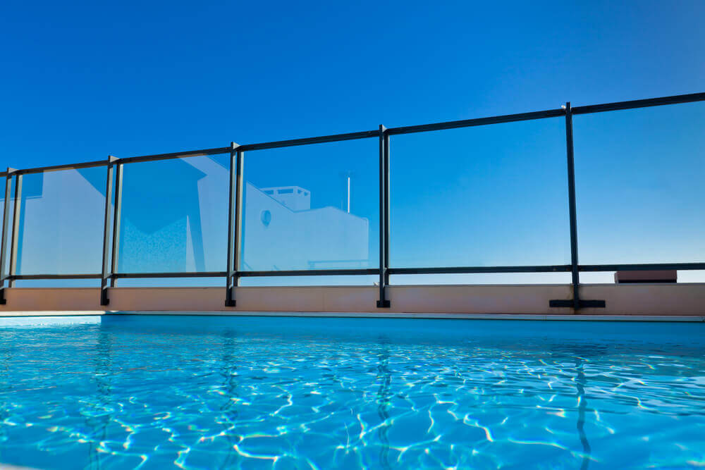 low angle shot from inside a pool looking up at a glass fence with a rich blue sky by pool fencing Toowoomba