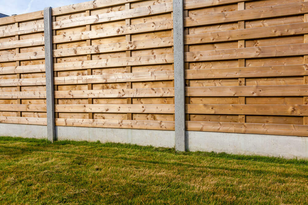 A large timber fence made of timber and steel support beams with grass infornt